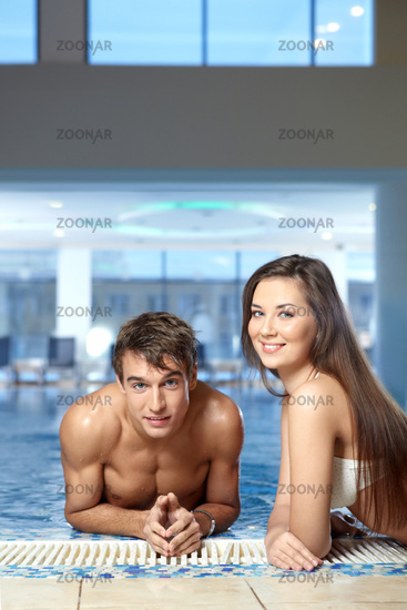 The girl and the young man smile against pool