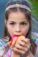 Cute 8 year old girl eating apple a cloudy day