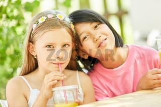 Zwei Mädchen als Freundinnen trinken Saft
