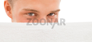 Young man behind white towel