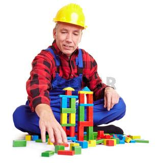 Bauarbeiter spielt mit Holzklötzen