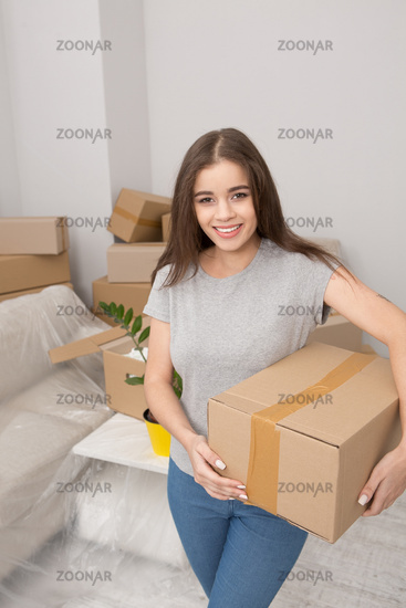 Young woman relocating, holding box ready to unpack things in newly rented apartment.