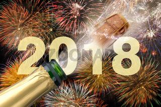 Champagnerflasche mit fliegendem Korken und Feuerwerk zu Silvester 2018