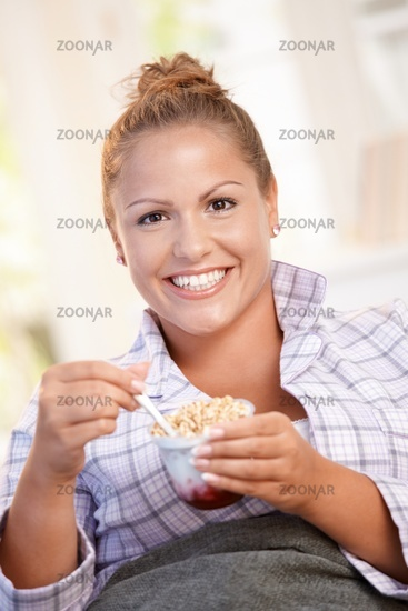 Young female having low fat breakfast in bed