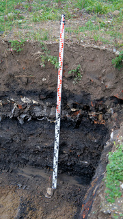 Former rubbish dump in the excavation pit, black discoloured and contaminated soil, old landfill in a construction site