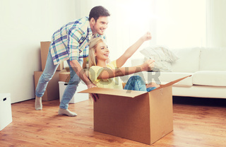 happy couple having fun with boxes at new home