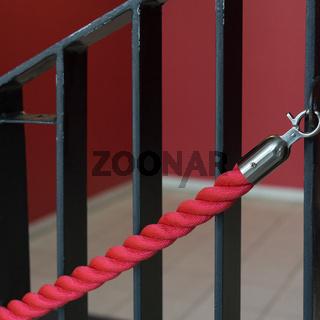 Rotes Absperrseil an einem Treppengeländer