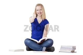 Junge hübsche Studentin sitzt lernt mit Büchern und zeigt Daumen