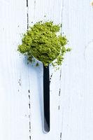 Matcha Grüner Tee auf Meßlöffel und weißem Holzhintergrund