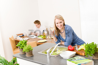 Happy woman cook enjoy wine in kitchen