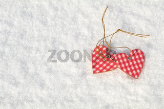 Beautiful valentine holiday background with two checkered motley hearts on white snow surface.