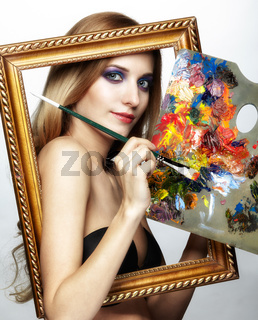 Young woman painter in golden frame with color pallet and paint brush in hand