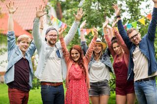 happy teen friends waving hands at summer garden