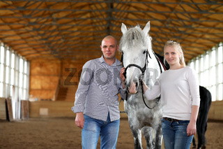 People on a horse training in a wooden arena
