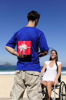 romantische Überraschung: Mann mit  Geschenk für seine Freundin im Rollstuhl