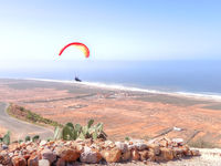 Paraglider flying over an arid coastal plain