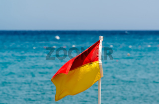 Red and yellow flag on beach on the background of the sea