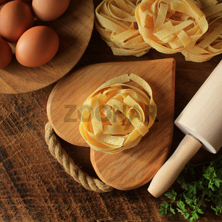 Raw italian pasta tagliatelle on wooden board and rolling pin on rustic background. Selective focus