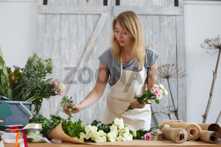 Young girl florist makes bouquet