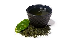 Tasse und Haufen grüner Shincha Tee der ersten Ernte mit Blatt.