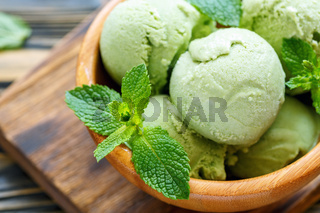 Balls mint ice cream and mint leaves closeup.