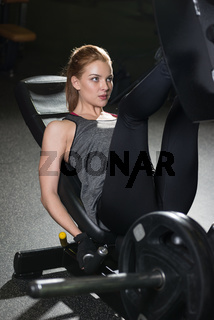 Sportive woman using weights press machine for legs. Gym.