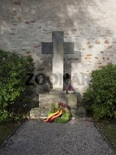 Niedergelegter Kranz vor einem Gedenkkreuz am Volkstrauertag