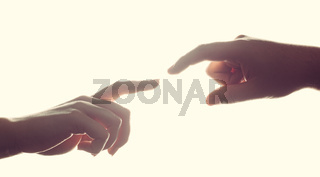 Man#39;s and woman#39;s hands, fingers reaching each other. Love, connect, help concepts.