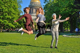 Beautiful girl jumping on the background of St. Isaac's Cathedral in the Park at Senate square