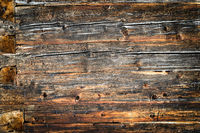 Old natural brown wood wall of log cabin. Wooden textured background pattern.
