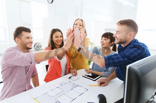 creative team making high five at office