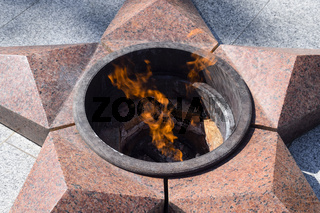 Burning of eternal fire. Five-pointed star made of granite memorial to the memory of killed soldiers