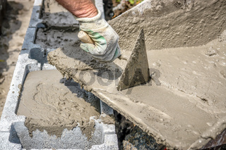 Closeup of mason hand pouring out mortar into concrete shuttering blocks from wheel-barrow