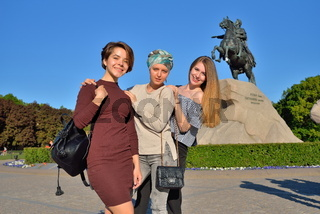 Three young girls are photographed on the background of the monument bronze Horseman in Saint-Petersburg