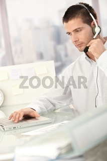 Young male dispatcher working in office