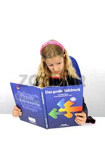 junge Schuelerin schaut entsetzt in ein Lehrbuch