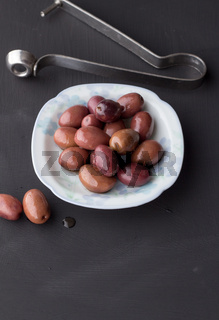 Purple olives in small white bowl with two on black chalk board texture background with olive pitter - vertical daylight shot with space for text