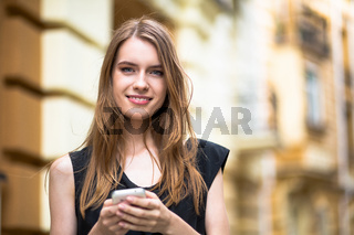 Close up portrait of smiling sensual girl holding cell phone in hands.