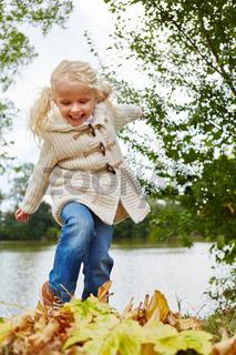 Blondes Mädchen spielt mit Herbstblättern