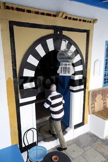 Ein Eingang in ein Cafe in der Altstadt von Sidi Bou Said in der Daemmerung am Mittelmeer und noerdlich der Tunesischen Hauptstadt Tunis.