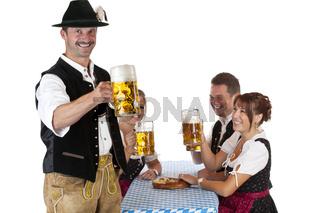 Bayrischer Mann mit Freunden prostet mit Oktoberfest Bier zu. Freigestellt auf weissem Hintergrund