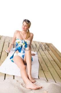Beach - woman sunbathing with pareo and sunglasses
