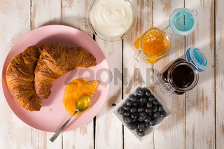 Breakfast with croissant and blueberries over a wooden table