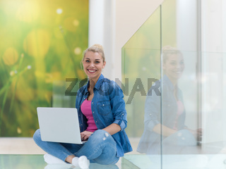 young woman using laptop computer on the floor