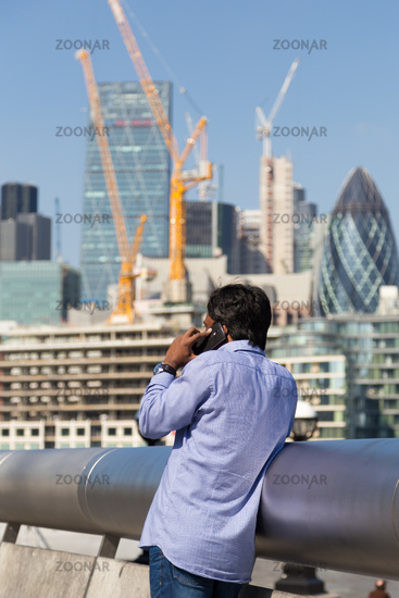 International businessman talking on mobile phone outdoor in London city, UK.