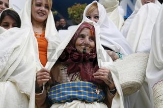 Ein Alte Fraue im traditionellen weissen Schleier in der Altstadt von Sidi Bou Said in der Daemmerung am Mittelmeer und noerdlich der Tunesischen Hauptstadt Tunis.