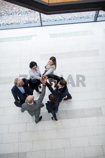Geschäftsleute im Kreis geben sich ein High Five