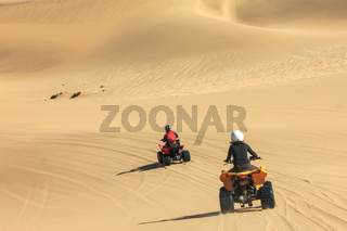 Quad driving people - two happy bikers in sand desert.