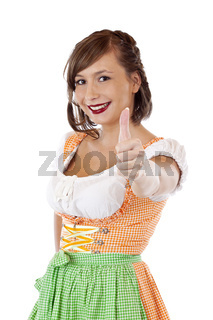 Fröhliche Frau im Oktoberfest Dirndl zeigt Daumen nach oben
