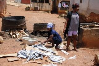 Ältere Frau bei Vorbereitung zum Grillen von Fisch